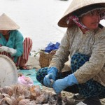 Women shelling shellfish by the shore in Mui Ne, Vietnam